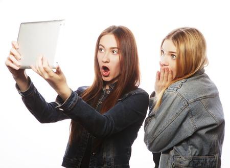 trato amable: Dos mujeres bastante jovenes que toman un autorretrato con una tableta, aislado en blanco Foto de archivo