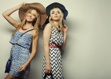 fashion: fashion concept: two sexy young women in summer fashion dress and straw hats, studio background