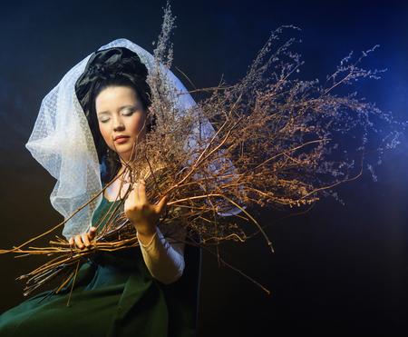 vestido medieval: chica en traje medieval con montón de palos en el humo