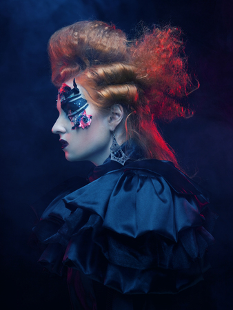 gothic woman: Gothic woman with red hair and bright make up.