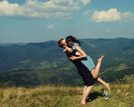 beach kiss: Beautiful young couple hugging and kissing on a summer holiday, Mountain, outdoors. Romantic travel and healthy lifestyle, exterior.