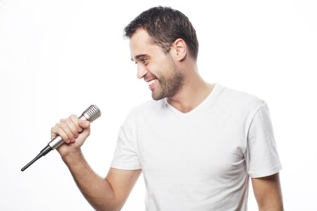karaoke: Life style, people and leasure concept: a young man wearing a white shirt holding a microphone and singing. Isolated on white.