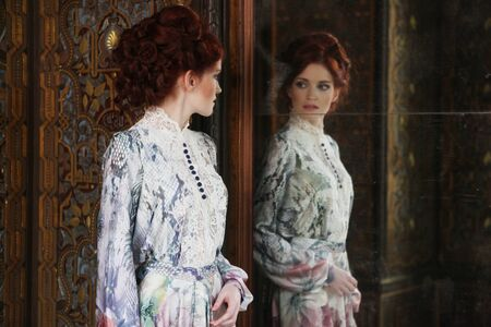 edwardian: Young beautiful woman standing in the palace room with mirror.