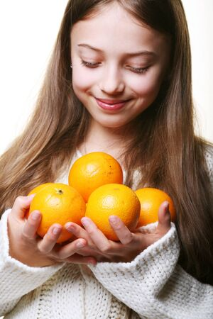 Girl child with an oranges