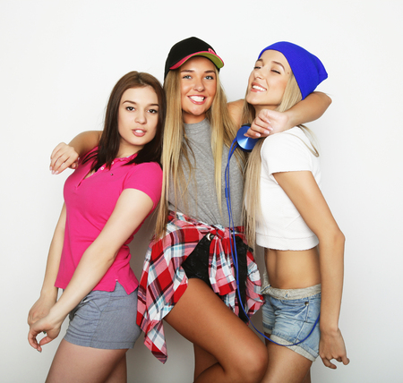 three women: Three stylish sexy hipster girls best friends.Standing together and having fun. Over gray background.