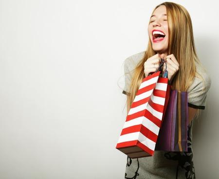 Portret van jonge gelukkig lachende vrouw met boodschappentassen, witte achtergrond
