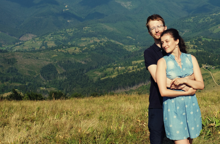 romantic sky: Beautiful young couple hugging and kissing on a summer holiday, Mountain, outdoors. Romantic travel and healthy lifestyle, exterior.
