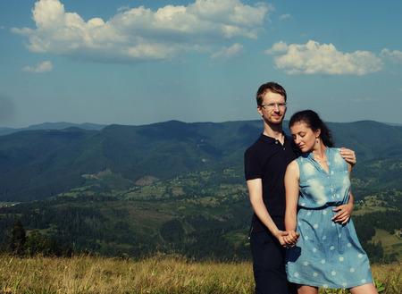 parejas romanticas: Hermosa joven pareja abrazándose y besándose en unas vacaciones de verano, la montaña, al aire libre. Viajes románticos y estilo de vida saludable, exterior. Foto de archivo