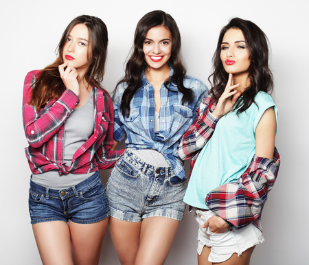 3 people: Three best friends posing in studio, wearing summer style outfit and jeans shorts. Girls smiling and having fun.