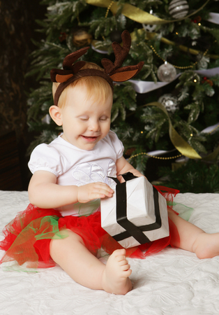 baby near christmas tree: Little baby girl with the gift box near  Decorating Christmas tree. Happy time.
