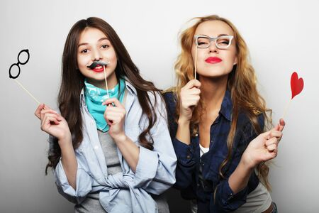 two stylish hipster girls best friends ready for party, over gray background