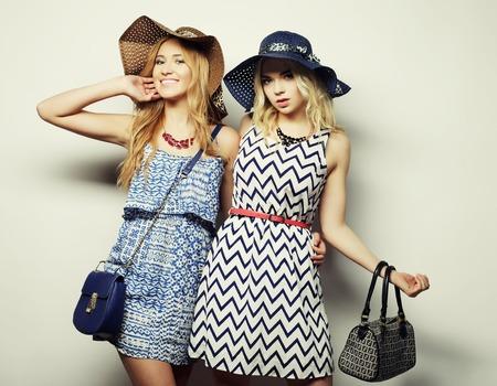 fashion concept: twee sexy jonge vrouwen in de zomer mode jurk en strooien hoeden, studio achtergrond