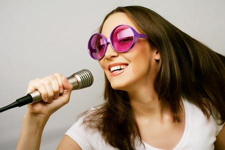 cantando: Chica cantante feliz. Mujer de la belleza vistiendo la camiseta blanca y gafas de sol grandes con micrófono sobre fondo blanco. ipster Styl