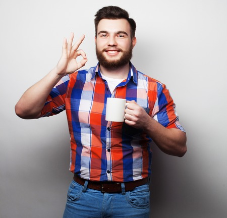 loony: food, happiness and people concept: young bearded man with a cup of coffee against grey background
