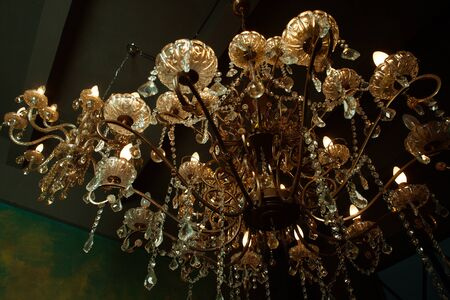 crystal chandelier: Beautiful vintage crystal chandelier in a room, Golden tones.