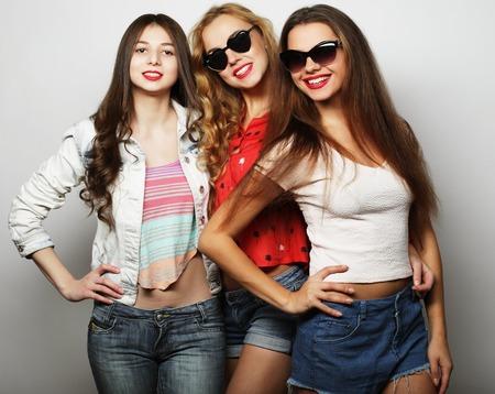 Tres mejores amigos que presentan en estudio, vistiendo traje de estilo de verano y pantalones cortos. Niñas sonriendo y divirtiéndose.