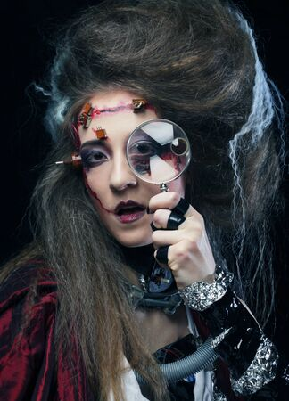 the scars: Young woman with creative make up holding a magnifying glass Stock Photo