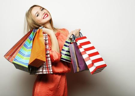 mujer alegre: Retrato de joven mujer feliz sonriendo con bolsas de la compra, sobre fondo blanco Foto de archivo