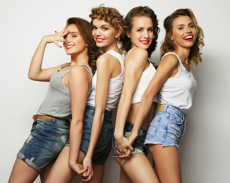 Fashion portrait of four stylish sexy hipster girls best friends, over gray background. Happy time for fun. 免版税图像