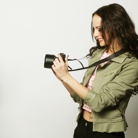 composing: Beautiful young woman with camera over gray background