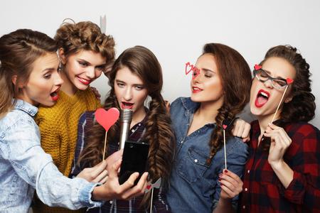 karaoke singer: group of  beautiful stylish hipster  girls singing karaoke