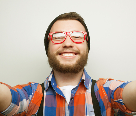 tehnology: Tehnology concept: Happy selfie. Handsome young man  holding camera and making selfie and smiling.