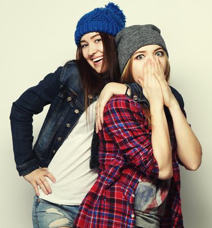 chicas adolescentes: Retrato de dos elegantes pastrulitas sexy mejores amigos, vistiendo trajes lindo botín y sombreros. Durante backround gris.