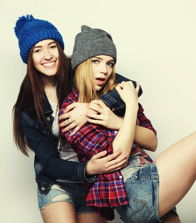 girls youth: Fashion portrait of two stylish sexy hipster girls best friends, wearing cute swag outfits and hats. Over gray backround.