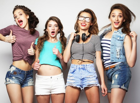 best friends girls: Fashion portrait of four stylish sexy hipster girls best friends, over gray background. Happy time for fun. Stock Photo