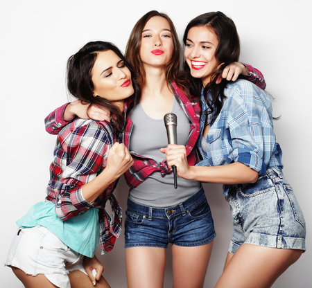 karaoke singer: life style, happiness, emotional and people concept: beauty hipster girls with a microphone singing and having fun Stock Photo