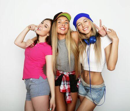 Tres elegantes chicas sexy inconformista mejores friends.Standing juntos y divertirse. Sobre fondo gris.
