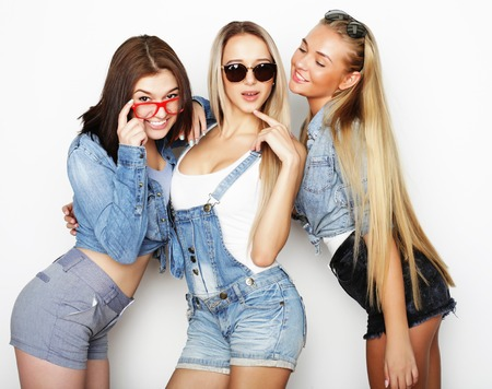 lifestyle and people concept: Fashion portrait of three stylish girls best friends, over white background. Happy time for fun.