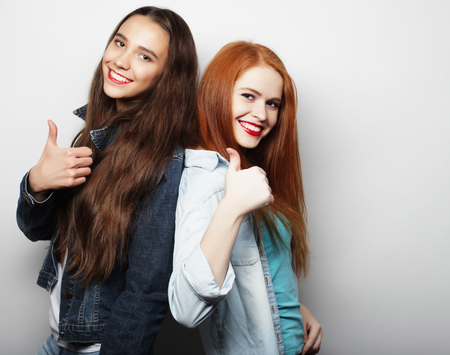 trendy girl: Two young girl friends standing together and having fun. Looking at camera.