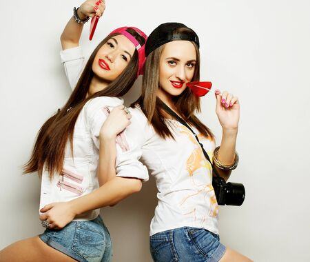 yo: Fashion portrait of two young pretty hipster girls wearing bright make up and holding candys. Studio portrait of two cheerful best friends sisters having fun and making funny faces. Stock Photo