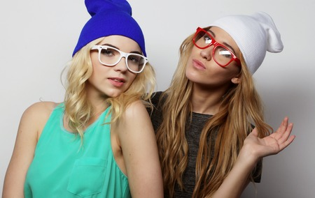 life style, happiness, emotional and people concept: Close up fashion lifestyle portrait of two young hipster girls best friends, wearing bright make up and similar trendy hats, making funny faces. Studio shot over grey background. Stock Photo