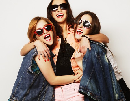 teenage love: Fashion portrait of three stylish sexy hipster girls best friends, over gray background. Happy time for fun. Stock Photo