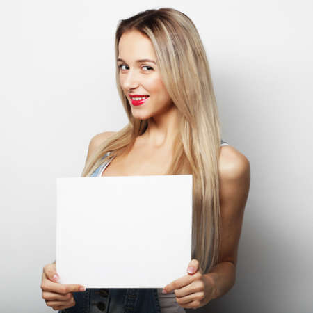 signboard: Smiling young casual style woman showing blank signboard, over white background isolated Stock Photo