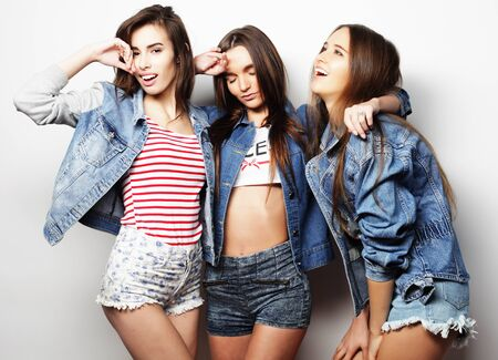teenage love: lifestyle and people concept:  Fashion portrait of three stylish sexy  girls best friends, over white background. Happy time for fun.