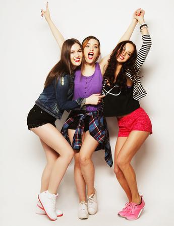drie gelukkige jonge meisjes vrienden dansen van vreugde in volle lengte, over grijze achtergrond Stockfoto