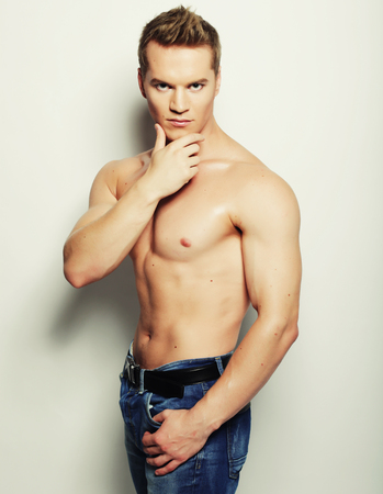hunk: Sexy fashion portrait of a hot male model in stylish jeans with muscular body posing