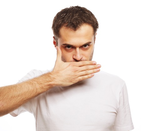 raised eyebrow: life style  and people concept: Shocked young man  covering mouth with hands and looking at camera while standing against white background Stock Photo