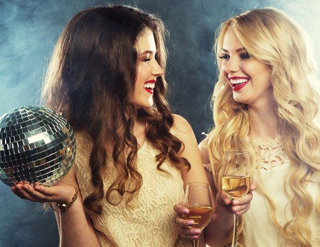 toasting wine: two beautiful young women with wine glasses and disco ball. Stock Photo