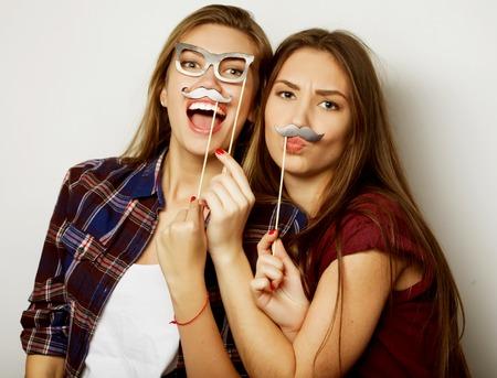 twee stijlvolle sexy hipster meisjes beste vrienden klaar voor partij, over grijze achtergrond Stockfoto