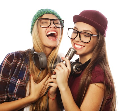 life style, happiness, emotional and people concept: two beauty hipster girls with a microphone singing and having fun 写真素材