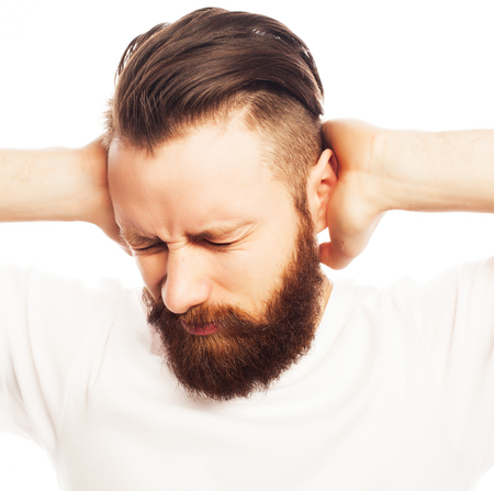 hands over ears: people, life style  and emotional  concept - bearded man covering his ears by hands over white  background