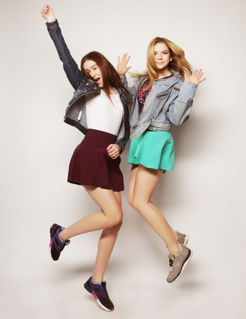 lifestyle portrait of two young hipster girls best friends jump over gray background Banco de Imagens