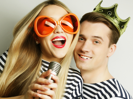flirtation: people, friendship, love and leisure concept - beautiful young loving couple with microphone. Big orange glasses and crown. Ready for party. Stock Photo