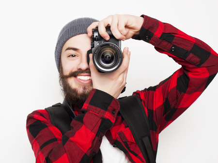 tehnology: life style, tehnology and people concept: professional photographer. Portrait of confident young man in shirt  holding  camera over white background