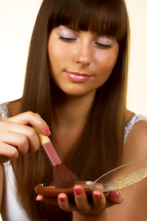 cheekbones: applying blusher isolated on white