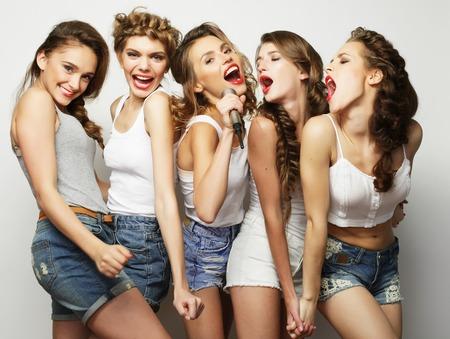 Gruppe der schönen stilvollen Hipster Mädchen singt Karaoke Standard-Bild - 53505435
